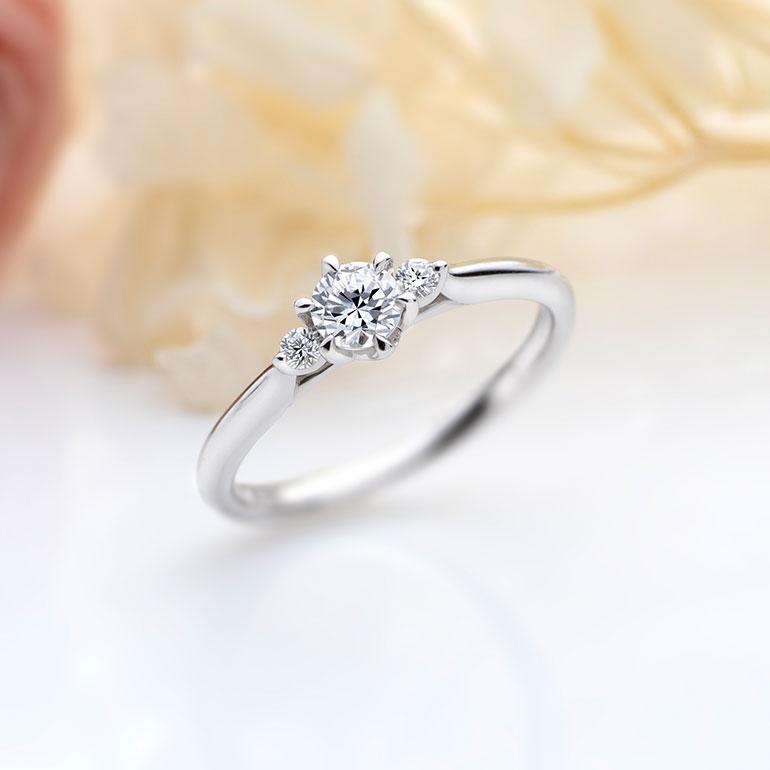 センターのダイヤモンドに花を添えるようにセットされた両サイドのメレダイヤモンドがより華やかな印象にしてくれます。正統派なデザインですが、サイドから見えるダイヤモンドを留めているシャトンデザインが繊細で可愛らしさも演出します。