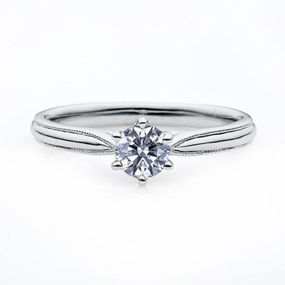 シンプルなソリティア(一粒石)タイプの婚約指輪。上下に施されたミル打ち加工がキュートな印象に。